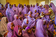 Members of the Mada Saving Club in Tsafe Nigeria greet a newborn child.  The Club is for women and has over 5500 members. Every week, women give money and when they need it, they can borrow with  a small interest not payable until after the first month.