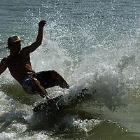 (02.02.2005)(PHOTO/CHIP LITHERLAND) -- Scott Romeo, 18, of Bradenton skims a wave at Holmes Beach, Florida, on Anna Maria Island Wednesday morning.