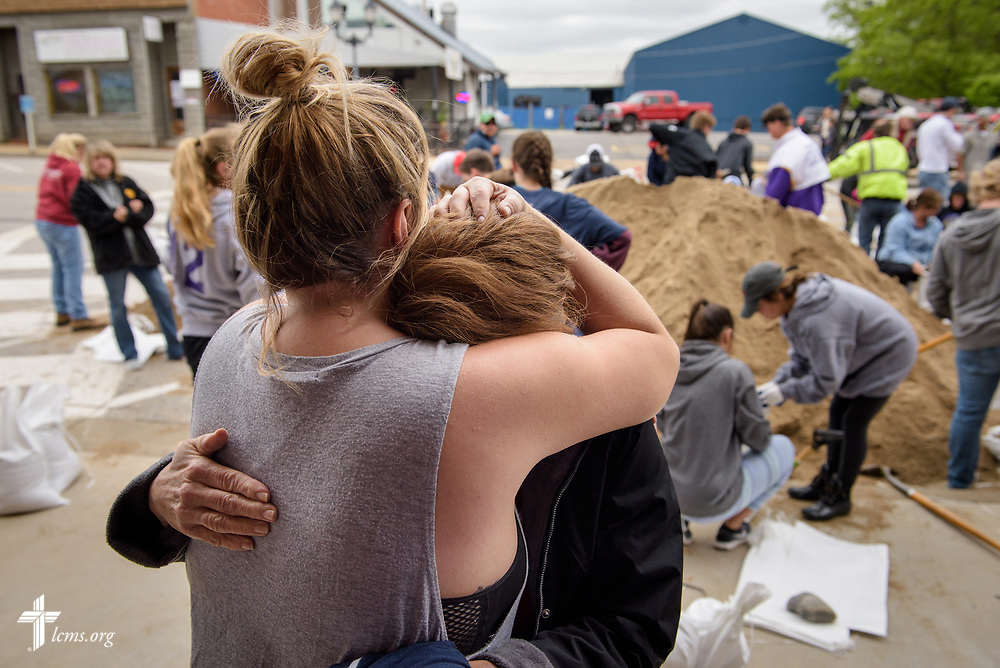 Church member Denise Kasten of St. Mark's Lutheran Ministries, Eureka, Mo., is comforted by a friend as volunteers from the church and community help fill sandbags to protect the town from rising floodwaters on Monday, May 1, 2017, in Eureka. LCMS Communications/Erik M. Lunsford