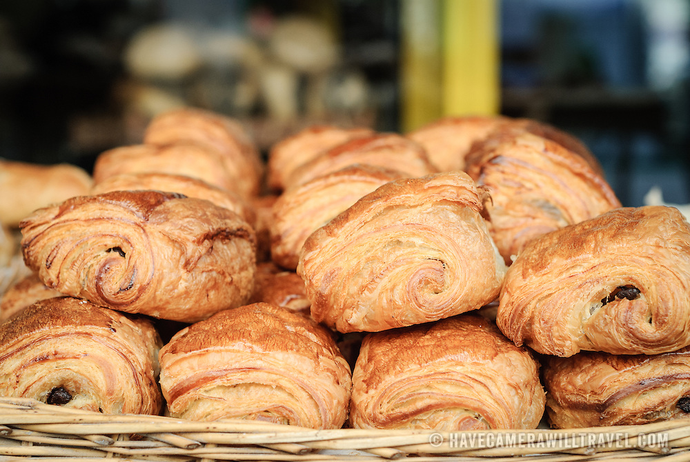 Freshly baked chocolate croissants (pain au chocolat) are stacked in a wicker basket for sale outside a bakery at the Mouffetard market in the Latin Quarter of Paris, France.