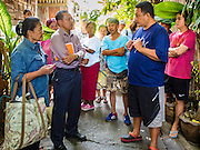 15 SEPTEMBER 2016 - BANGKOK, THAILAND:  A resident of Pom Mahakan (far left) and a city official (second from left) listen to a Pom Mahakan community leader say goodbye to the resident on the day she moved out of the slum. She accepted money from Bangkok city government and left voluntarily. Forty-three families still live in the Pom Mahakan Fort community. The city of Bangkok has given them provisional permission to stay, but city officials say the permission could be rescinded and the city go ahead with the evictions. The residents of the historic fort have barricaded most of the gates into the fort and are joined every day by community activists from around Bangkok who support their efforts to stay.                     PHOTO BY JACK KURTZ