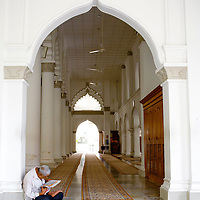 Reading the newspaper at the Kapitan Keling Mosque on Chulia St., George Town, Penang. One of the oldest mosques in Penang.