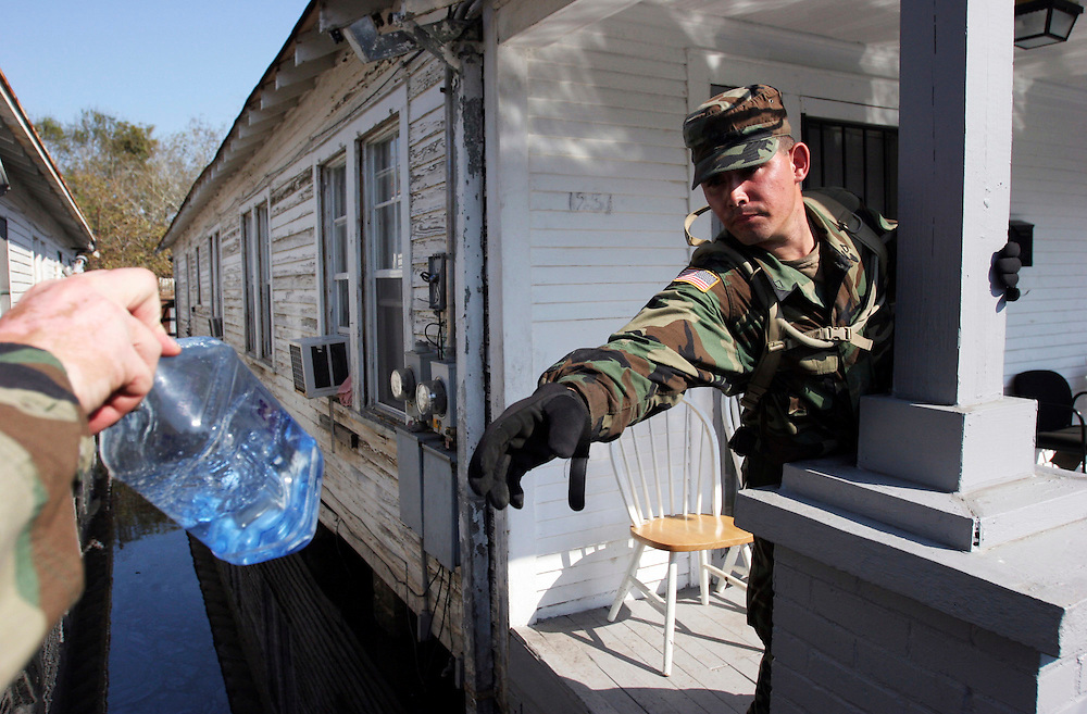 PFC Donald Epperson (right) passes a bottle of water to another guardsman to give to an abandoned dog while searching for survivors in the flooded homes of New Orleans. Oregon National Guard troops work in New Orleans after the wrath of Hurricane Katrina. Photographed September 8, 2005. (Thomas Patterson / Statesman Journal)