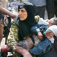 A Shiite woman holds her lifeless baby, moments after a series of bomb blasts outside of the Imam Abbas holy shrine in Karbala, Iraq, which killed over 100 people. March 2004.