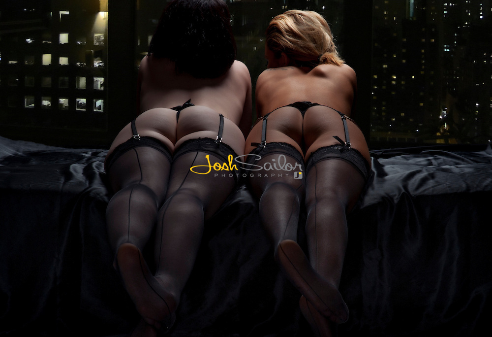 Two girls laying side by side in bed together at night, looking out of an apartment window at a glistening city.