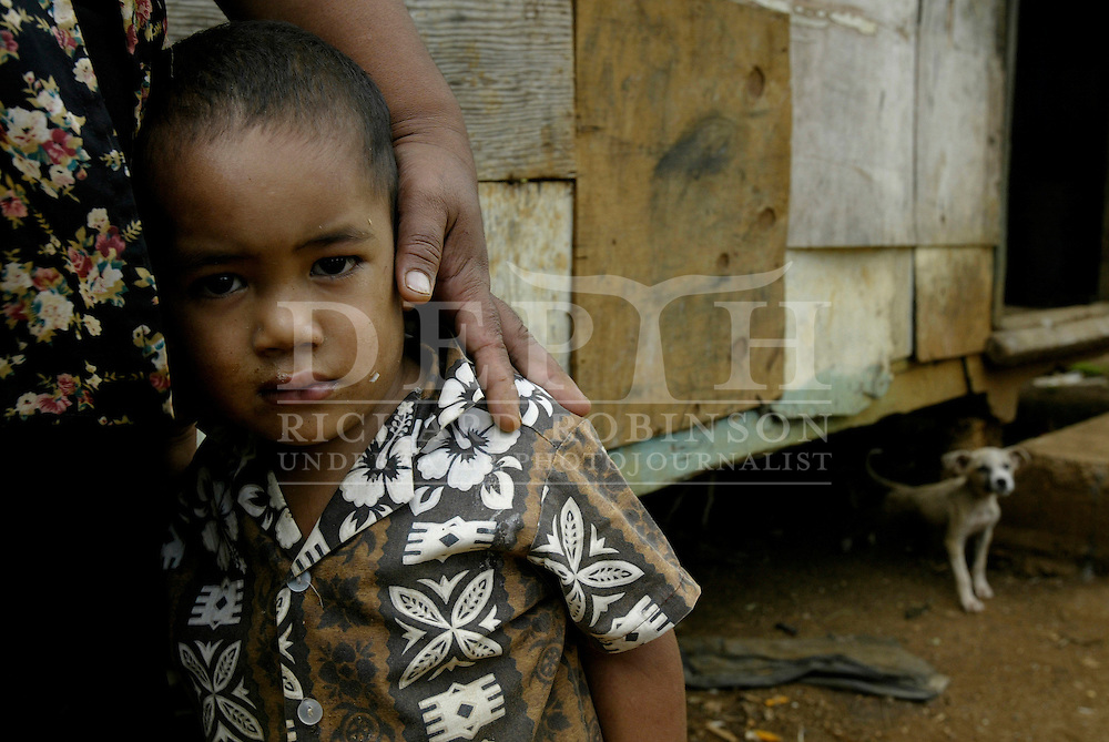 2-year-old Paul stays close to his mother Sivihiva Tokoma'ata outside their small one room home that sleeps nine in the village of U'tungake on the island of Vava'u in Tonga. They receive about $100 dollars a year in remittance from her brother in New Zealand who has nine children of his own.<br /> Photograph Richard Robinson. May 2004.<br /> 2004 &copy; New Zealand Herald A Division of APN New Zealand Ltd.<br /> No Reproduction without prior written permission. Contact www.newspix.co.nz to licence photograph.