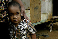 2-year-old Paul stays close to his mother Sivihiva Tokoma'ata outside their small one room home that sleeps nine in the village of U'tungake on the island of Vava'u in Tonga. They receive about $100 dollars a year in remittance from her brother in New Zealand who has nine children of his own.<br />