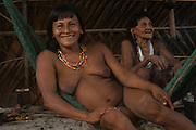 Huaorani Indian, Kope Tega relaxing in her hammock inside her hut. This is usually the only furnishing in the huts.<br /> Bameno Community. Yasuni National Park.<br /> Amazon rainforest, ECUADOR.  South America<br /> This Indian tribe were basically uncontacted until 1956 when missionaries from the Summer Institute of Linguistics made contact with them. However there are still some groups from the tribe that remain uncontacted.  They are known as the Tagaeri &amp; Taromenane. Traditionally these Indians were very hostile and killed many people who tried to enter into their territory. Their territory is in the Yasuni National Park which is now also being exploited for oil.