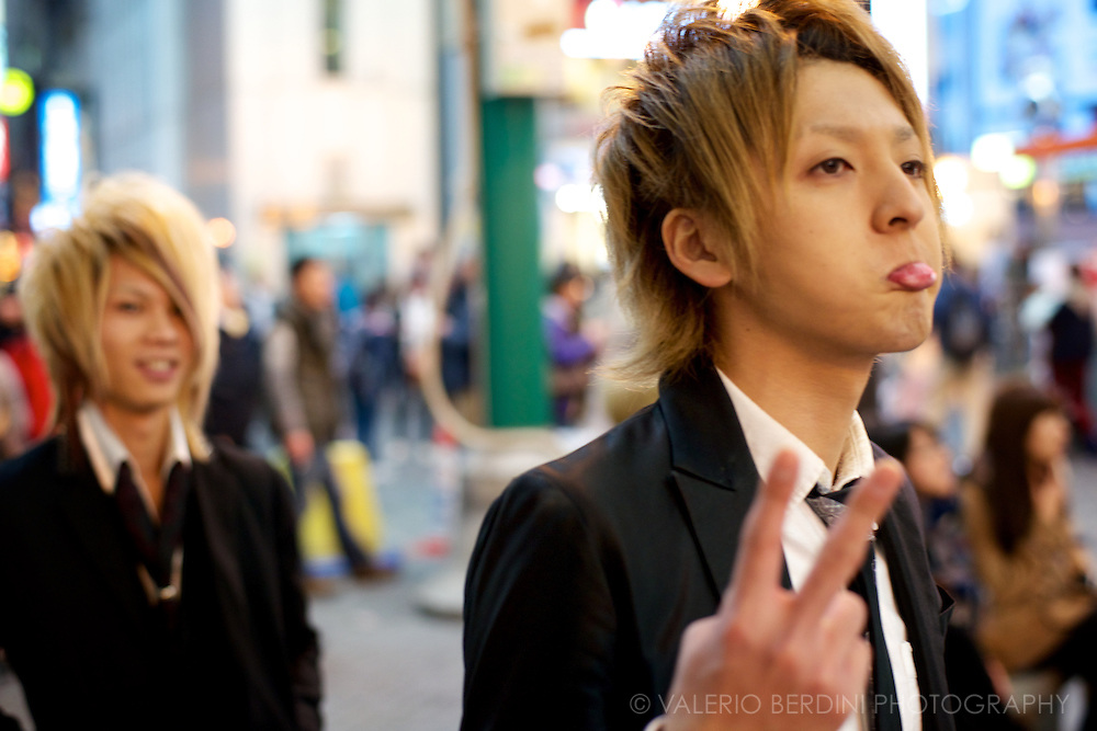A teenager pulls a face when realises I am portraying him. His friend smiles in the back. Osaka, Japan 2013