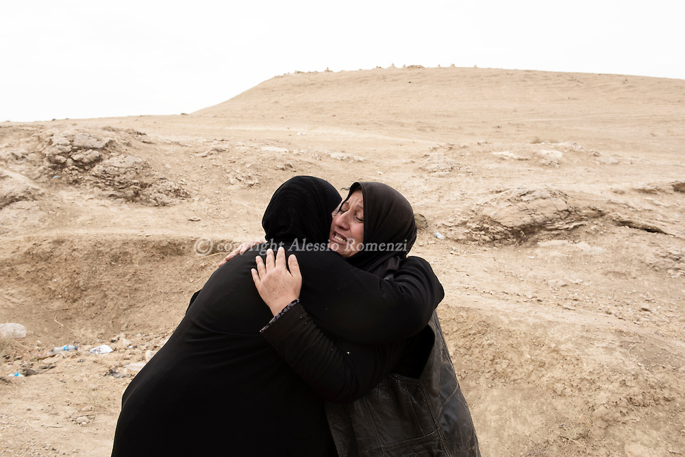 Iraq, Nineveh Governorate: About ten kilometres from Al Shura, newly displaced Iraqi hug each other as they arrive on the western bank of the Tigris river escaping their villages occupied by IS on November 2016. Alessio Romenzi