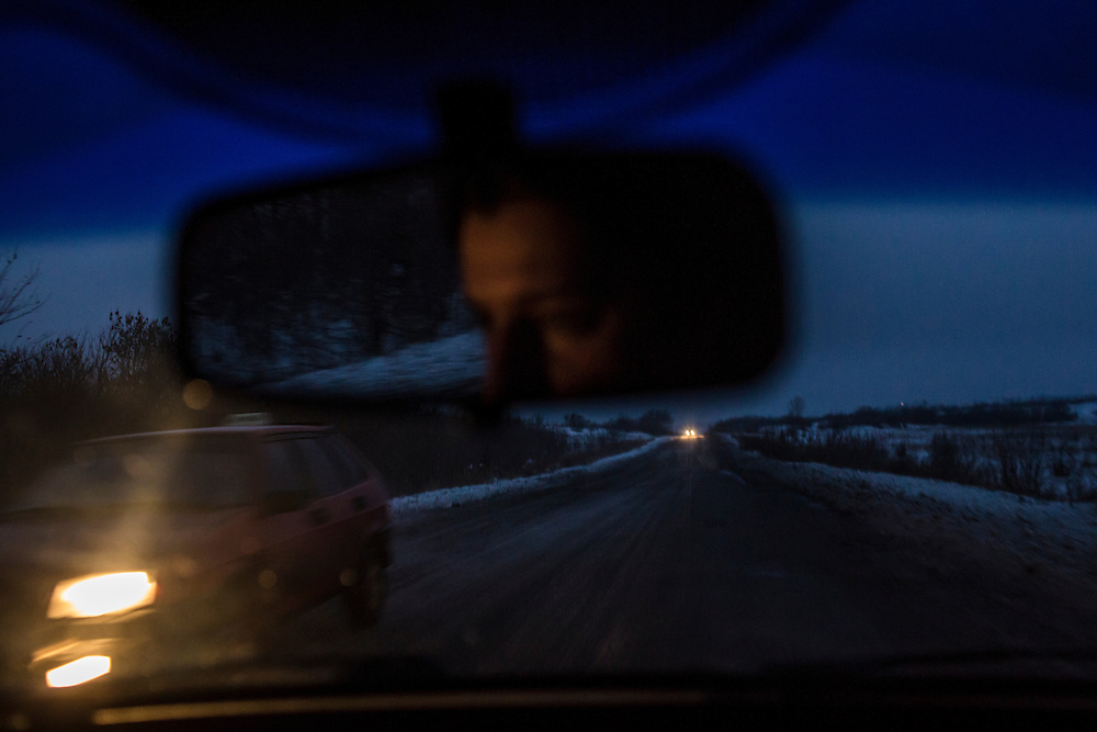 KRASNYI LUCH, UKRAINE - DECEMBER 8, 2014: Cars pass on a road at dusk near Krasnyi Luch, Ukraine. CREDIT: Brendan Hoffman for The New York Times