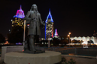 Lighted downtown buildings with d'Iberville statue in Cooper Riverside Park.