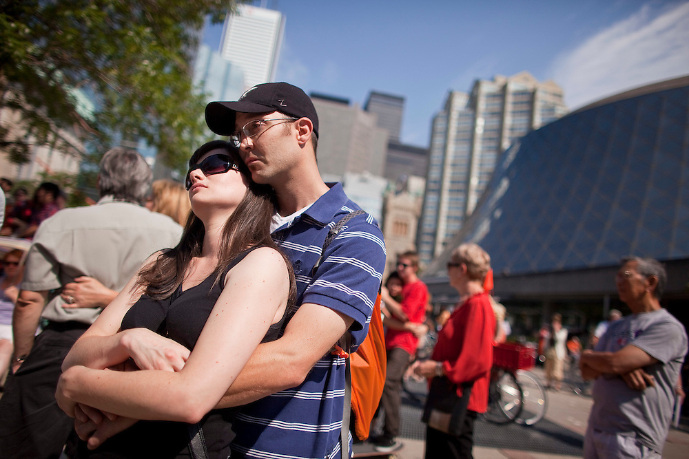 Toronto, Ontario ---11-08-27--- A couple listens to the state funeral for NDP leader Jack Layton, broadcast to thousands gathered outside Roy Thompson Hall in Toronto, Ontario, August 27, 2011. <br /> AFP/GEOFF ROBINS/STR