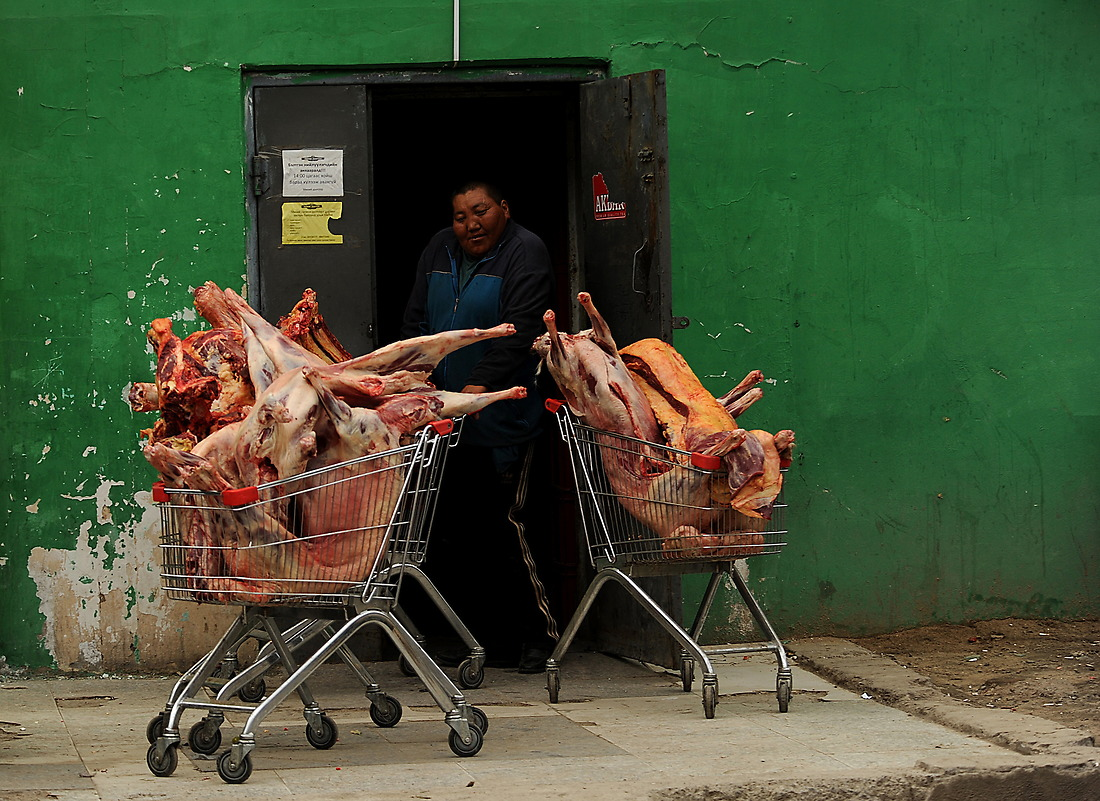 At the back door of a local butcher shop, a Mongolian butcher pulls in shopping carts of meat after unloading them from his car in Ulaanbaatar. — © Jeremy Lock/USAF