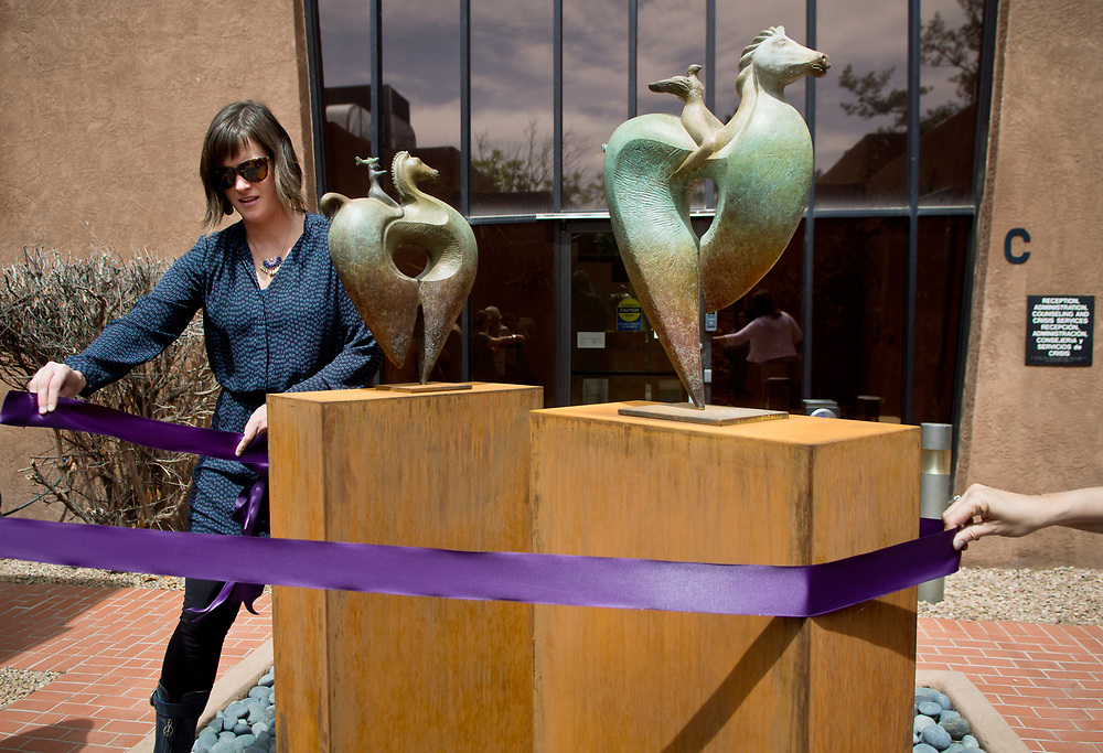 """mkb041117b/metro/Marla Brose -- Nan Masland, Bernalillo County's public art project coordinator, wraps a purple ribbon around the bronze sculpture, Bird Ryders, which was installed inside the courtyard of the Rape Crisis Center of Central New Mexico, and was dedicated Tuesday, April 11, 2017, in Albuquerque, N.M. The pieces were funded by Bernalillo County 1% for the Arts. """"My goal is that they offer hope,"""" said Enrico Embroli who created the sculpture. (Marla Brose/Albuquerque Journal)"""