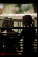 Two young women chat by Cafe & Companhia's window. Here it's possible to buy and drink coffee grown in the islands.