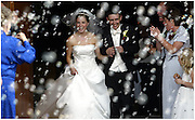 A thrilled bride and groom exit the church to cheers and bubbles blown by family and friends.