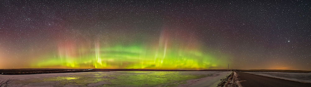 A roughly 160&deg; panorama from northwest to east, of the aurora display of March 2, 2017 over a nearby frozen pond south of home in southern Alberta. Despite the pond being frozen the aurora still reflects in the bare ice. <br /> <br /> Arcturus is at right above the county road duw east, with Jupiter and Spica to the far left. Perseus and the Milky Way are at far left. <br /> <br /> This is a stitch of 6 segments, each 13 seconds at f/1.8 with the Sigma 20mm Art lens and Nikon D750 at ISO 3200. Stitched with Adobe Camera Raw.