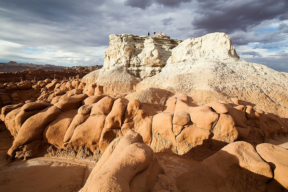 Hikers stand on the summit of a high mesa overlooking the vast field of hoodoos at Goblin Valley State Park, Utah.