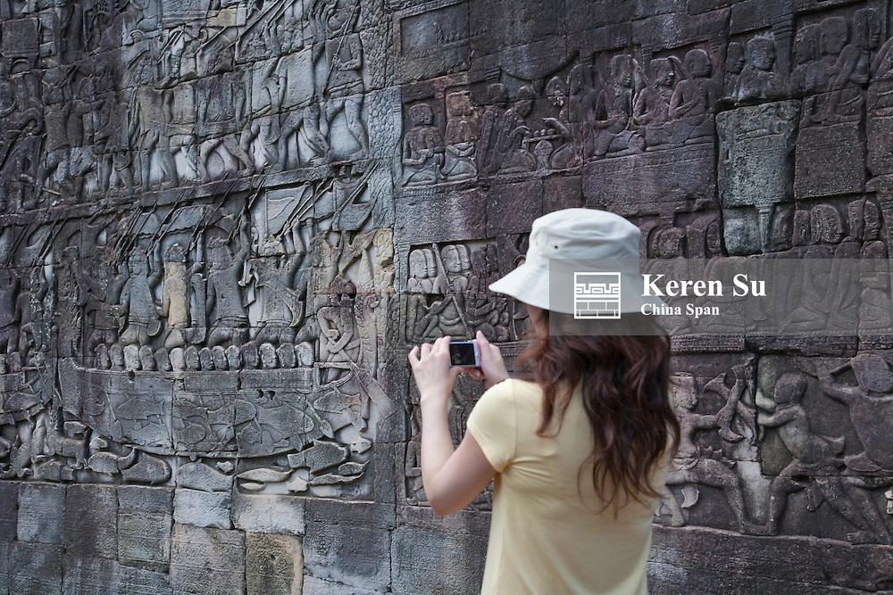 Tourist photographing at Bayon Temple, Angkor Thom, UNESCO World Heritage site.