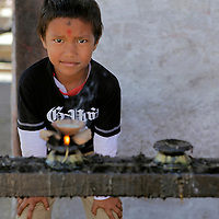 Asia, Nepal, Kathmandu. Young boy lights candle at Hindu Temple.