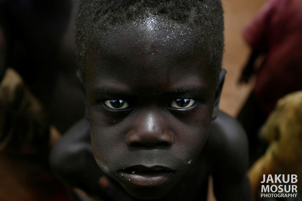 October 7, 2006 - A child looks up while chewing sugar cane in Tetugu camp for internally displaced people, or IDP, near Gulu in north Uganda. Tetugu, with a population of 22,000, is one of 76 IDP camps around Gulu, the main base for the Uganda Peoples Defense Force fighting the insurgent Joseph Kony's Lord's Resistance Army. Kony's LRA movement has been fighting for the past 20 years to force the East African country to be ruled according to the Christian Ten Commandments. Over 2 million people, mostly of the Acholi tribe, have moved or were forced to move from their villages to camps close to the towns of Gulu, Lira, and Kitgum where they are watched over by the Ugandan Army. The LRA rebels have abducted thousands of children and have forced them to fight against the Ugandan Army and the Acholi people. Current peace talks between Kony's LRA and the Ugandan government held in Juba, southern Sudan, offer a glimpse of hope to ending this ongoing conflict..(Photo by Jakub Mosur/Polaris)<br />