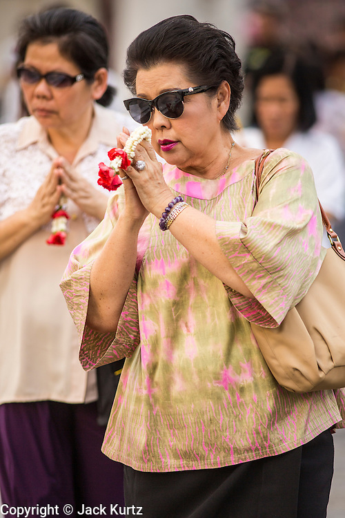 """25 FEBRUARY 2013 - BANGKOK, THAILAND: Thai women bow their heads as they enter Wat Benchamabophit Dusitvanaram (popularly known as either Wat Bencha or the Marble Temple) on Makha Bucha Day. Makha Bucha is a Buddhist holiday celebrated in Myanmar (Burma), Thailand, Cambodia and Laos on the full moon day of the third lunar month (February 25 in 2013). The third lunar month is known in Thai is Makha. Bucha is a Thai word meaning """"to venerate"""" or """"to honor"""". Makha Bucha Day is for the veneration of Buddha and his teachings on the full moon day of the third lunar month. Makha Bucha Day marks the day that 1,250 Arahata spontaneously came to see the Buddha. The Buddha in turn laid down the principles his teachings. In Thailand, this teaching has been dubbed the 'Heart of Buddhism'.      PHOTO BY JACK KURTZ"""