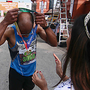 Charles Powell II (3060) of Bel Air, MD., puts on his medal after finishing the 13th Annual Discover Bank Delaware Marathon Sunday, May 8, 2016, at Tubman Garrett Riverfront Park, in Wilmington Delaware.