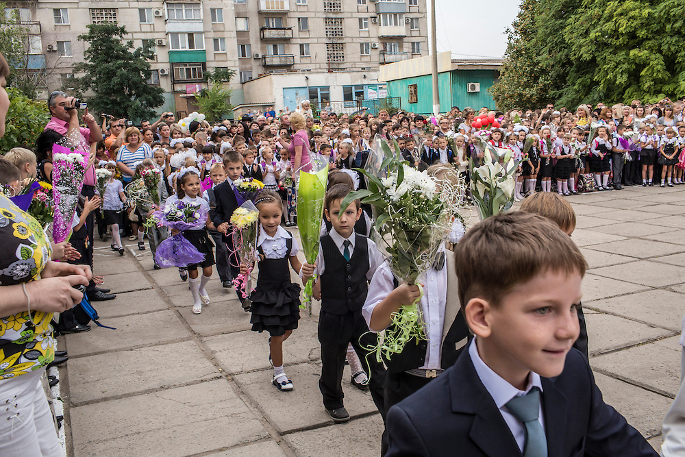 MARIUPOL, UKRAINE - SEPTEMBER 1, 2015: Students in the first class at School 68 are welcomed during a ceremony for the first day of the new school year in Mariupol, Ukraine. On January 24 of this year, shelling in the same neighborhood killed 31 people, all civilians, and while much recent fighting has been concentrated near Mariupol, a drop in ceasefire violations in the past few days has been credited to a desire to not interfere with the start of the new school year. CREDIT: Brendan Hoffman for The New York Times