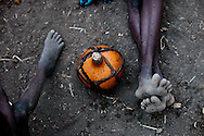 A gourd of milk sits on the ground between a mother and her child. The Boma hospital is the only in the region.