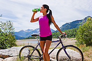 A woman taking a break from mountain biking to refresh herself with a drink