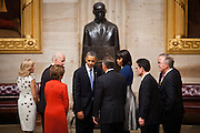 Accompanied by Vice President Joe Biden, congressional leaders and their spouses, President Barack Obama turns away from a statue of Martin Luther King Jr. after a moment of reflection in the US Capitol Rotunda after the inaugural luncheon, January 21, 2013 in Washington, D.C.