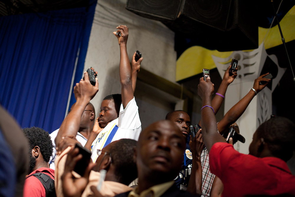 Journalists hold cell phones and microphones near a speaker while Richard Dumel, Provisional Electoral Committee (CEP), reads the results of the January 28th election. The results are suspected by many to be fraudulent.