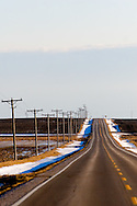 A newly paved yet lightly trafficked highway disappears over the hills in the distance on the flat plains of north central Illinois.