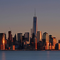 New York City skyline photography image of the FIDI, short for the finanacial district, in downtown New York photographed on a beautiful winter evening minutes before sunset. The New York City World Trade Center is a complex of buildings in Lower Manhattan. The skyscraper is replacing an earlier complex of 7 buildings with the same name on the same site. The original World Trade Center featured landmark twin tower, were destroyed in a tragic terrorist attack on 11 September 2001. The new site is now a rebuilt with six new skyscrapers with a 911 memorial to those killed in the terrorist attacks. One World Trade Center is the tallest skyscraper in the United States.<br />