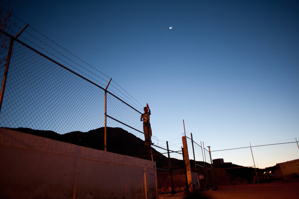 A young man climbs the fence to a soccer field in the Diaz Ordaz colonia, one of the poorest communities of Ciudad Juarez. Within the last two months one of their members was murdered.