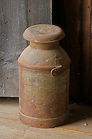 An antique metal milk container stands outside a cow barn at Shaker Village  in Hancock Massachusetts.