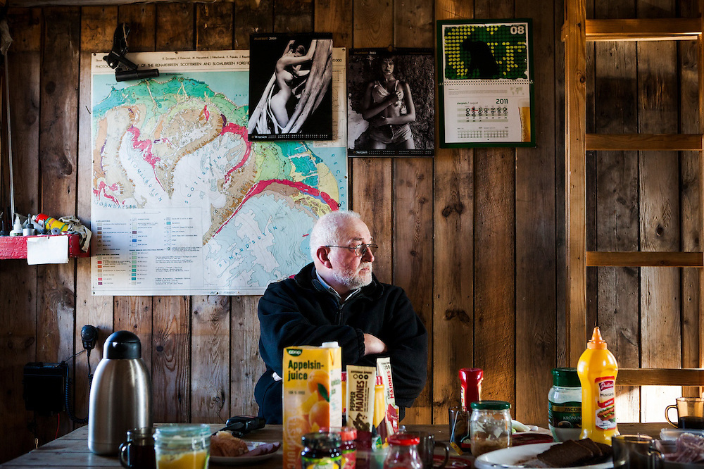 Polish glaciologist Jacek Jania waits restlessly for high winds to subside in the comfort of the Polish field station in Calypsobyen, Svalbard. A geological map and pinup girl Playboy calendars adorn the wall behind him.