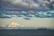 """Mt. Baker, covered in 188"""" of snow this season, glows in the sun as seen from Port Angeles, about 60 miles away to the west. The clouds in between over the Strait of Juan de Fuca look ominous. The ship is the MV Coho, a ferry that runs between Port Angeles, WA and Victoria BC."""