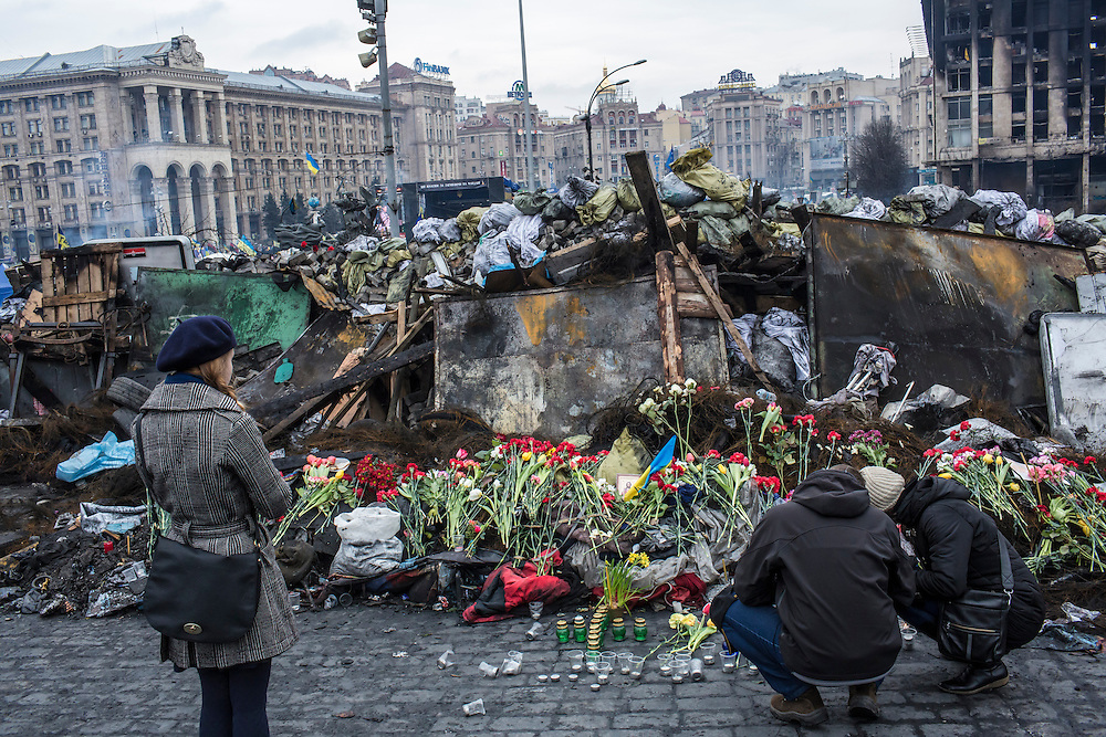 KIEV, UKRAINE - FEBRUARY 23: People place flowers at a memorial to anti-government protesters killed in chashes with police on Independence Square on February 23, 2014 in Kiev, Ukraine. After a chaotic and violent week, Viktor Yanukovych has been ousted as President as the Ukrainian parliament moves forward with scheduling new elections and establishing a caretaker government. (Photo by Brendan Hoffman/Getty Images) *** Local Caption ***