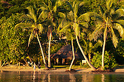 Couple on beach in front of bure guest room at Matangi Private Island Resort, Fiji.