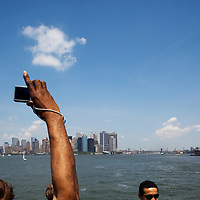 USA, New York, New York City, Young man's hand reaches up to take snapshots of Manhattan skyline from Staten Island Ferry on spring morning