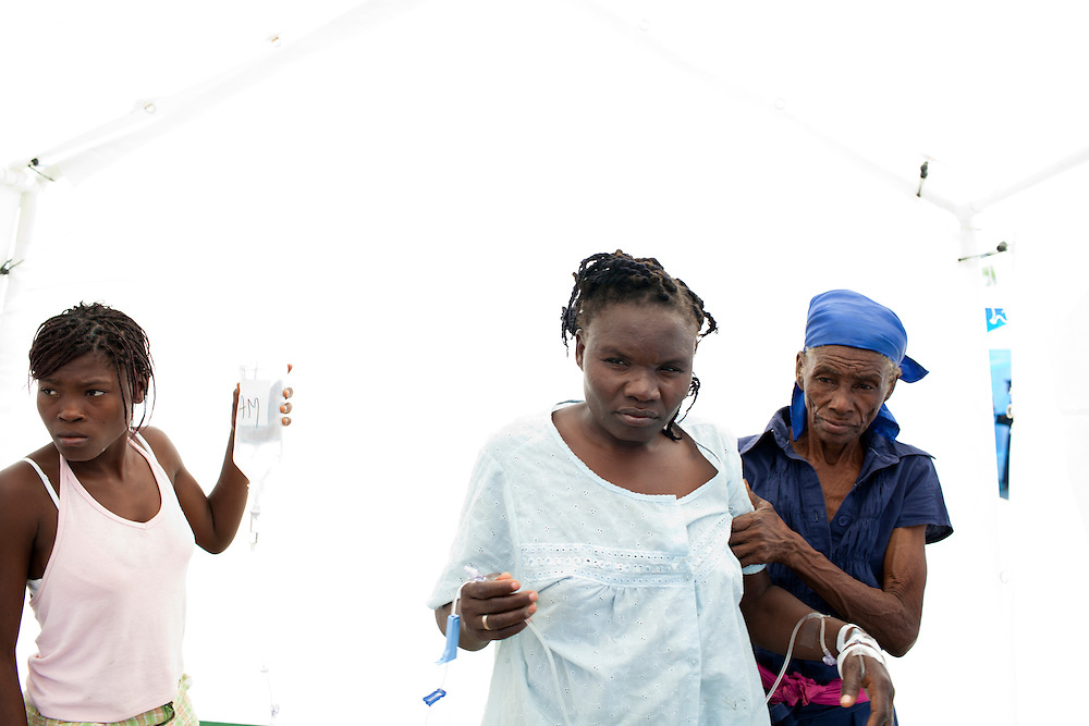 Adel Egzi, center, is helped to the restroom while being treated for cholera at a clinic on Friday, November 26, 2010 in Cabaret, Haiti.