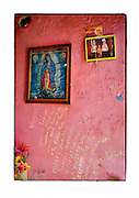 "SHOT 2/6/15 11:51:54 AM - A roadside capilla in the mountains just outside of Mascota, Mexico and featuring Nuestra Señora de Guadalupe as well as pictures of loved ones and personal notes. The Virgin of Guadalupe has symbolized the Mexican nation since Mexico's War of Independence. Our Lady of Guadalupe (Spanish: Nuestra Señora de Guadalupe) is a celebrated Catholic icon of the Virgin Mary also known as the Virgin of Guadalupe (Spanish: Virgen de Guadalupe). The Lady of Guadalupe is of significant importance to Mexican Catholics and has been given the titles of ""Queen of Mexico"", ""Empress of the Americas"", and ""Patroness of the Americas"". Roadside capillas, or tiny chapels, are common along the roads and highways of Mexico which is heavily Catholic and are often dedicated to certain patron saints or to the memory of a loved one that has passed away. Often times they contain prayer candles, pictures, personal artifacts or notes. (Photo by Marc Piscotty / © 2015)"