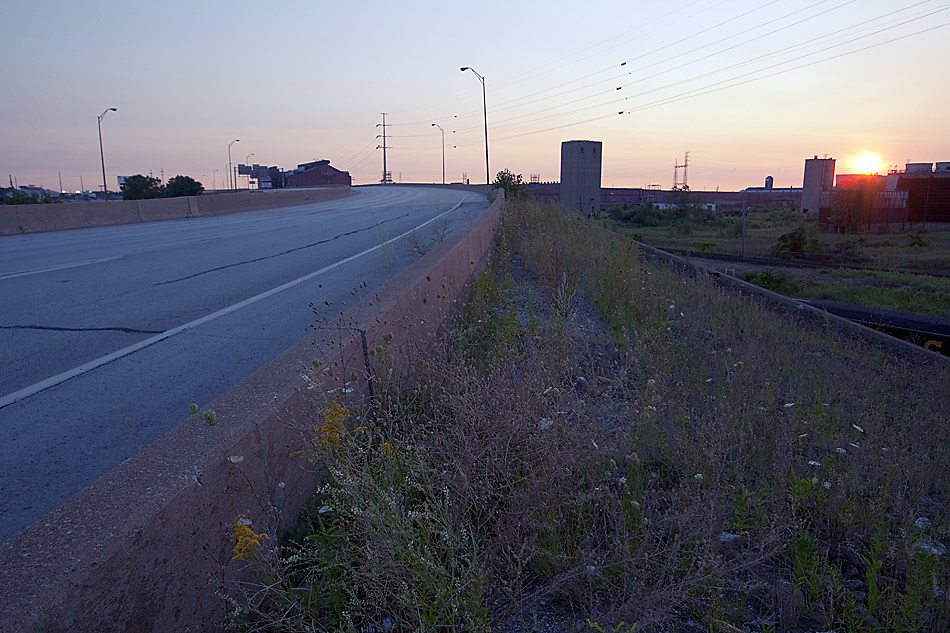 The shrubbery along the abandoned section of Cline Avenue in East Chicago grows wild now as the sun sets behind a few industrial buildings.