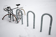 A ten speed bike is locked up tight to it's rack, and it's not going anywhere anytime soon, as it's also buried under a heavy dose of snow.