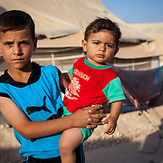 Ibrahim, 7, holding his cousin, Khalid, 16 months. Zaatari Camp for Syrian Refugees, Jordan, August 2013.