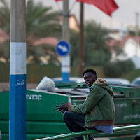 """A Sudanese refugee seats under red flags in the city of Eilat on  February 28 2011. The municipality hung 1,500 red flags around the city as a sign of warning and put up hundreds of banners reading: """"Protecting our home, the residents of Eilat are drawing the line on infiltration."""" Eilat Mayor Meir Yitzhak Halevi said that 10 percent of the city's population was currently made up of migrants and that the residents feel that the city has been conquered...Photo by Olivier Fitoussi."""