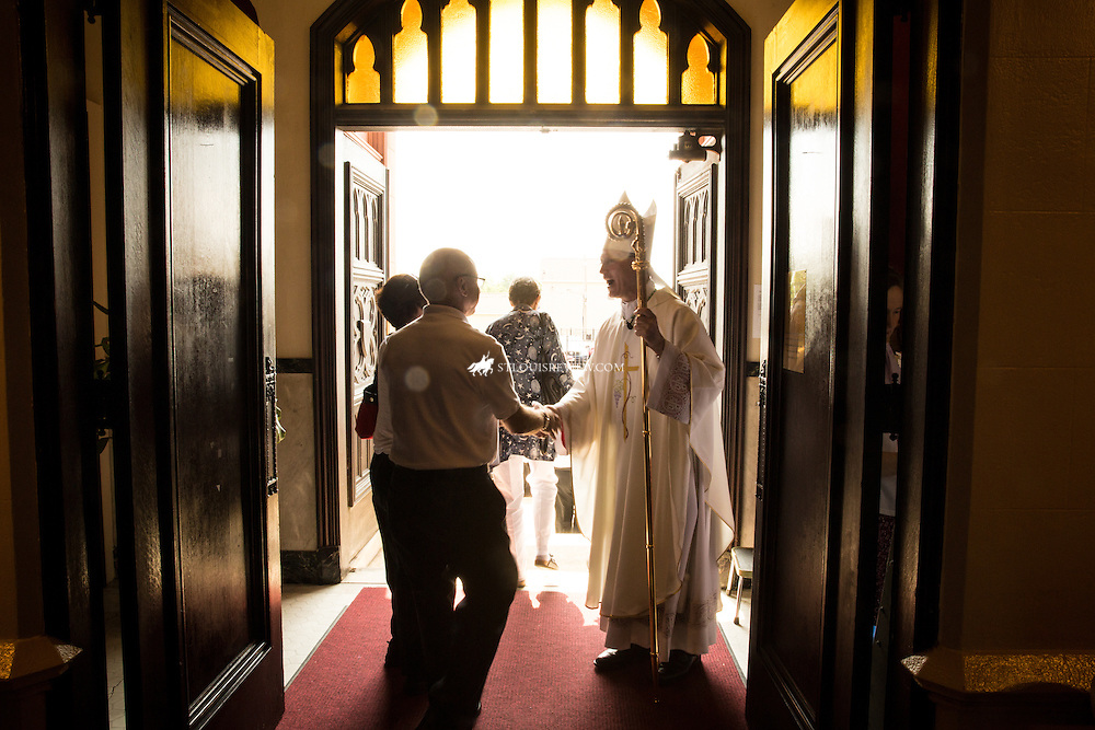 """Lisa Johnston   lisajohnston@archstl.org    Twitter: @aeternusphoto  Bishop Edward Rice greeted everyone as they left the church.   A """"Mass Mob"""" was held on the solemnity of Corpus Christi at Visitation St. Ann Shrine in north St. Louis. The parish is a blending of three parishes, the former Holy Ghost and St. Ann and Our Lady of the Visitation. The parish holds a novena to St. Ann each year, honoring the grandmother of Jesus and their St. Vincent dePaul Society has a significant outreach to those who are experiencing corporal needs."""