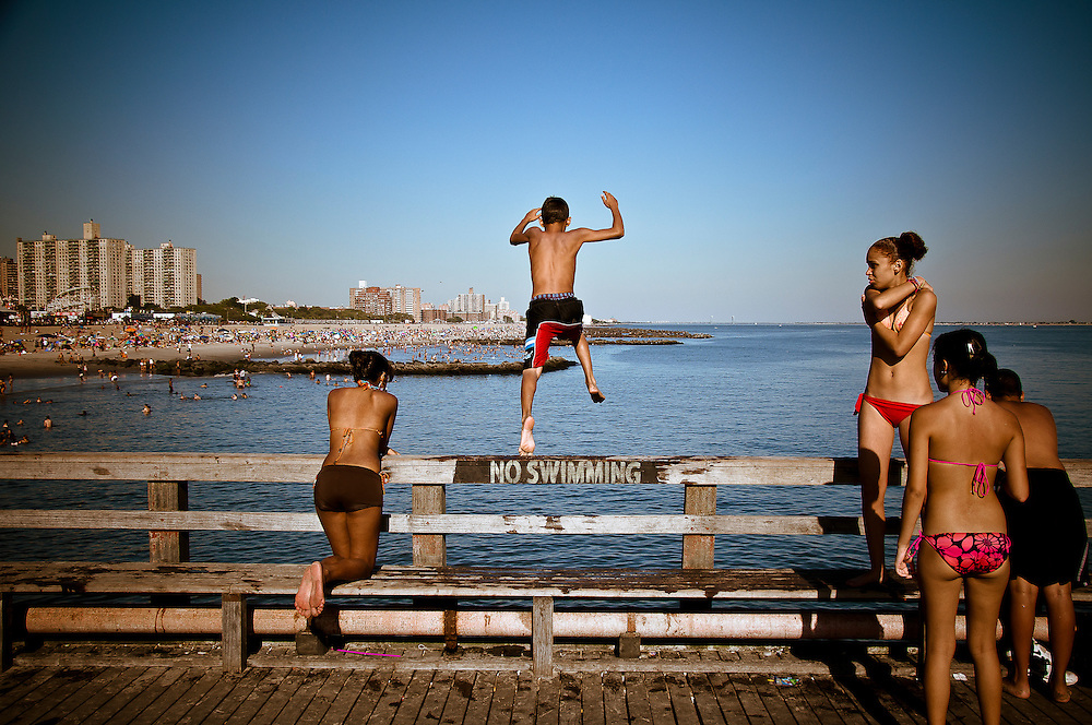 A kid jumps into the water from the coney Island pier, despite the No swimming sign, Brooklyn, New York, 2010.